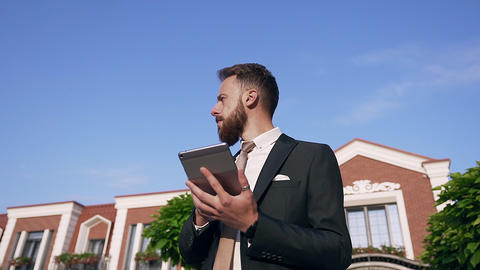Portrait of serious businessman with well groomed beard and tablet in hands Live Action