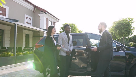 Elegant bearded man showing a black car for african american man and european Footage