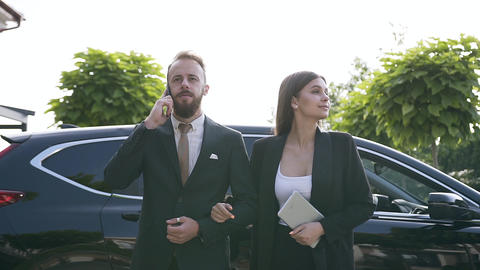 Slow motion of the business man and woman in strict costumes walking on the Live Action