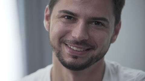 Portrait of handsome smiling man in white t-shirt sitting at home smiling while Live Action