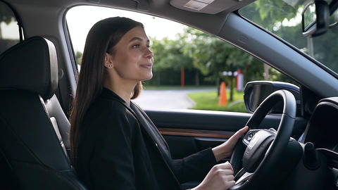Portrait of beautiful young businesswoman sitting on the driver's seat,looking Live Action