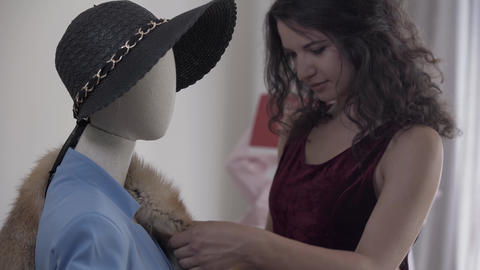 Attractive female seller putting fox skin on the shoulder of a mannequin in the Live Action