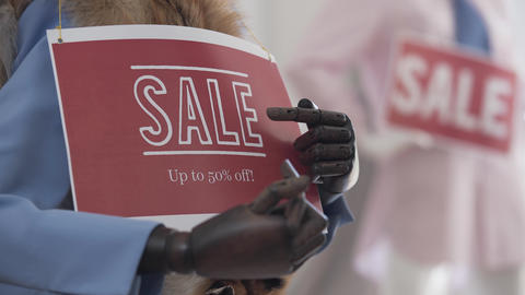 Female hands hanging a sign on a mannequin. Sale of mannequins Live Action