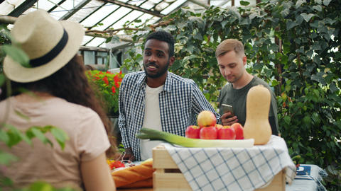 Cheerful youth purchasing organic food in market talking to sales girl Live Action