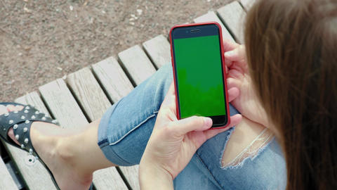 Beautiful girl holding black smartphone in the hands of a green screen, hand of Live Action