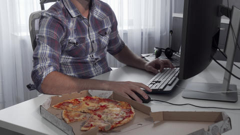 Handsome man enjoying tasty pizza while working on a computer Footage