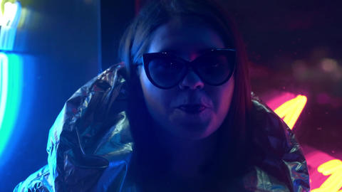 Young fashion teen girl in fur glasses blowing bubble gum illuminated with Footage