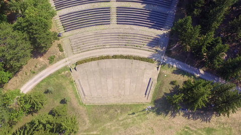 Aerial drone footage of amphitheater in the park surrounded with trees Live Action