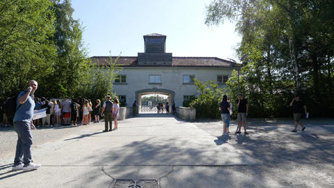 Tourists in front of the historic entrance to the Dachau concentration camp Footage