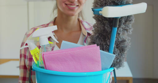 Cleaning concept. Young woman holds basin with washing fluids and rags in hands Live Action