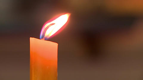 A candle burns with a yellow flame in the Church, the flame sways, blurred background Live Action