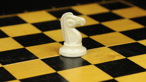 Rotation. Chess figure white horse on chess board. Close-up Footage