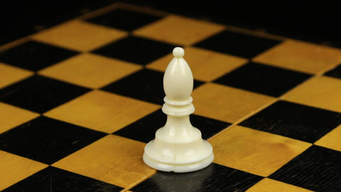 Rotation. Chess figure white bishop on chess board. Close-up Footage