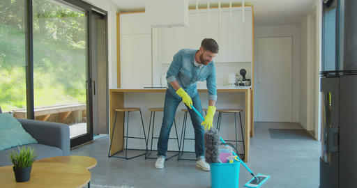 Man is mopping floor at home and having fun. Man, joy and houses concept Footage