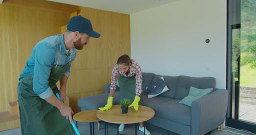 Positive smiling professional cleaners doing cleanup in ordinary apartment Live Action