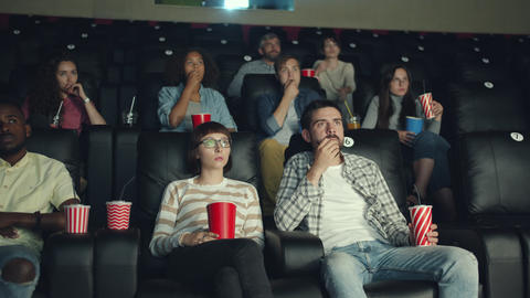 Emotional viewers enjoying scary thriller in cinema watching film with attention Footage