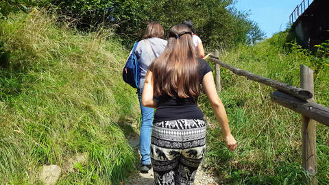 Girls climb up a forest mountain path with wooden railing, Live Action