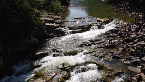 Water stream flow among stones. Clear water quickly fall downhill flowing around Live Action