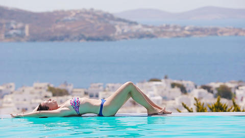 Beautiful young girl relaxing in the swimming pool outdoors with beautiful view Footage