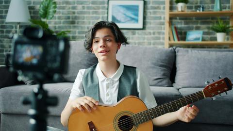 Teenage boy recording video for online vlog holding guitar talking gesturing Live Action