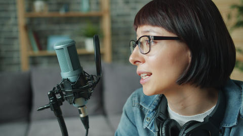Cheerful young lady talking recording audio using microphone in apartment Footage