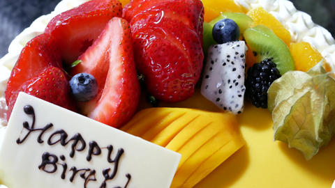 Motion of fruit birthday cake on a black background with 4k resolution Live Action