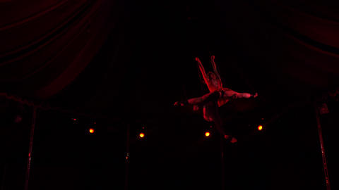 Two acrobats soaring under circus dome at night Footage