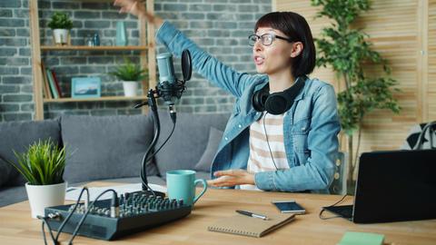 Emotional woman speaking gesturing recording audio in microphone at home Footage