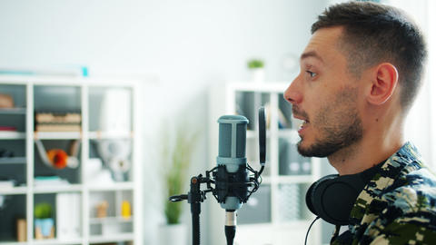 Close-up of male blogger recording audio podcast for online blog talking in mic Live Action