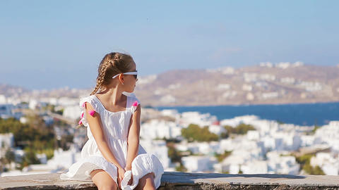 Portrait of adorable little girl background Mykonos town in Europe Footage
