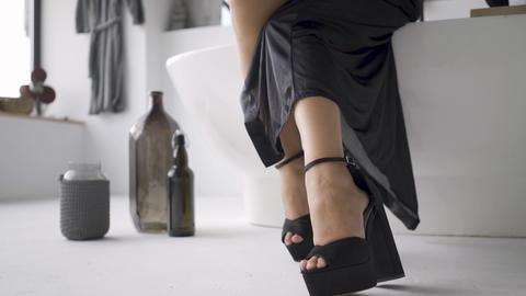 Feet of young woman in elegant black clothes with slim body sitting on teh bath Footage