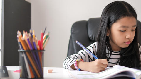 Asian little girl doing homework select focus shallow depth of field Live Action