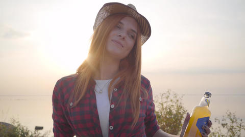 Portrait of beautiful hipster girl throwing up cold bottle of beer or limonade Footage