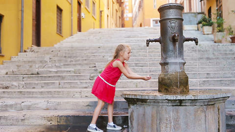 Little adorable girl drinking water from the tap outside at hot summer day in Footage