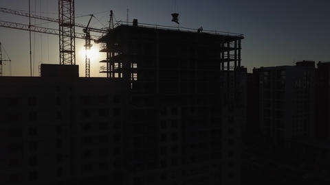 Construction Site at sunset. Silhouette of a construction crane near the Footage