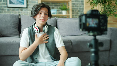 Cheerful teenager talking gesturing in front of camera recording video for vlog Live Action