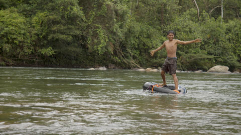An Indigenous Boy Plays In A Water With A Floating Tire In Ecuador Live Action