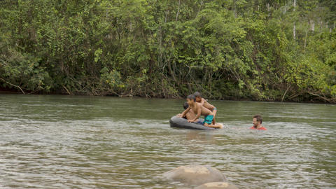 Indigenous Boys And An Adult Are Playing In A River With A Floating Tire In Ecuador Live Action