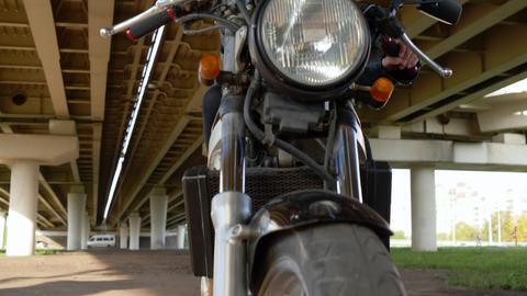 Young biker girl in leather jacket posing on black motorcycle under car bridge Footage