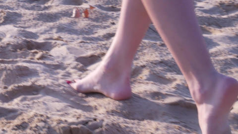 Female lags walking barefoot on the beach Live Action