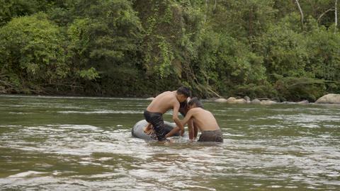 Indigenous Boys Plays In A Water With A Floating Tire In Ecuador Live Action