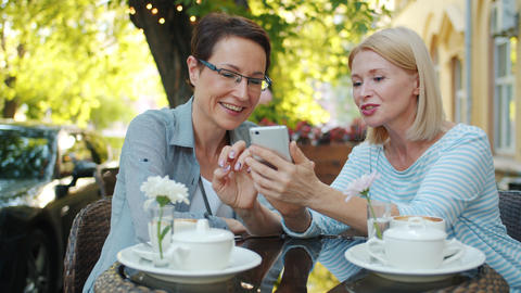 Happy ladies laughing chatting looking at smart phone screen in outdoor cafe Footage