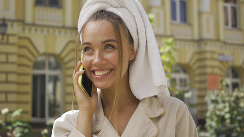 Portrait smiling young woman in bathrobe with towel on head talking by cellphone Live Action