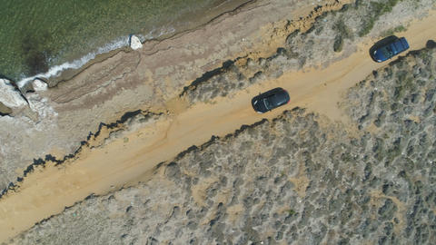 Top view of two cars driving alone sea coast line in Lemnos, Greece Footage