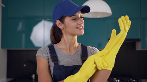 Beautiful smiling woman from cleaning service wearing protective gloves to clean Live Action