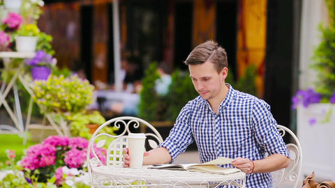 Caucasian young european man in outdoors cafe. Portrait of attractive young Live Action