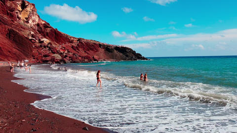 Tourists enjoying the beautiful turquoise water at the Red beach, Santorini, Cyclades island, Greece Live Action