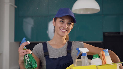 Pretty 30s girl in cleaning clothes spraying the green detergent on the Footage