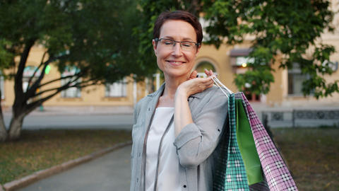 Slow motion portrait of mature lady holding shopping bags smiling outside Footage
