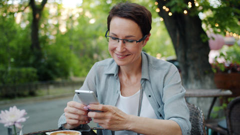 Smiling lady using smartphone touching screen smiling in street cafe outside Footage